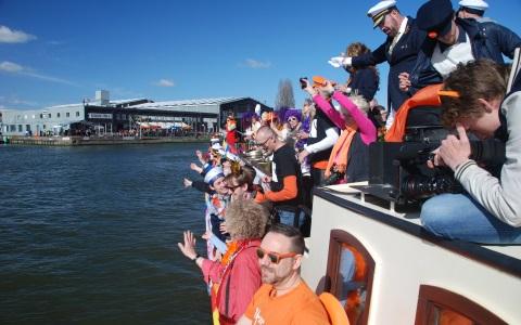 een evenement met mensen met oranje kleding op het dek van schip de Sailboa Rederij Navigo