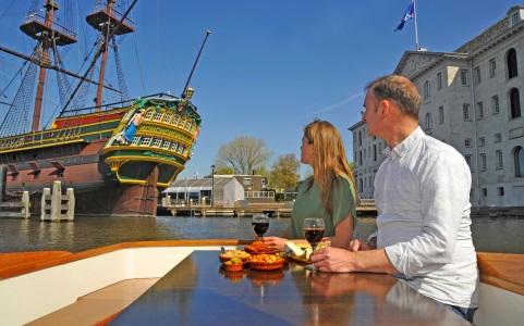 gasten aan boord van Salonboot Amber kijken naar het museumschip de Amsterdam VOC Schip bij Het Scheepvaartmuseum Amsterdam