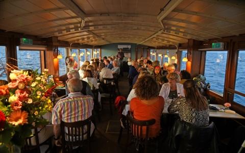 Mensen dineren aan boor van Salonboot Elvira Rederij Navigo